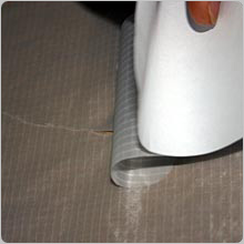 Carefully roll the patch onto the tear whilst holding the material either side taught.